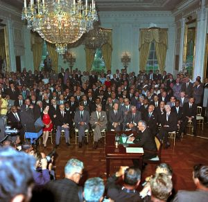 L.B. Johnson signs civil rights act